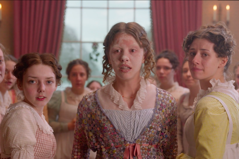 Emma's best friend Harriet Smith, played by Mia Goth, looks concerned, face covered in flour. She stands at the center of a group of concerned-looking young women .