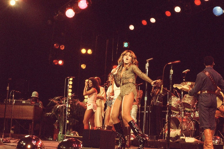 A woman in knee-high black heeled boots  sings and dances on stage. She is wearing a gold, sparkly leotard; behind her is a gold drum set. A man, his back to the camera, plays guitar to her left. Three woman are to her right, singing backup; to their right is a man at a keyboard playing alongside them.