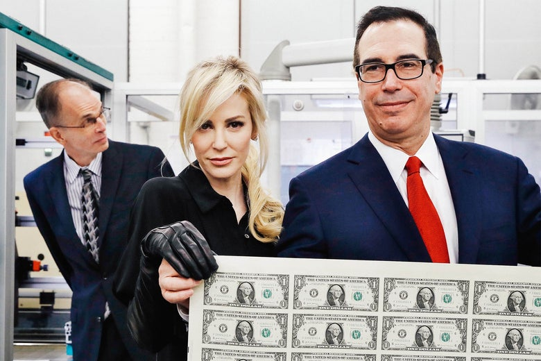 Treasury Secretary Steve Mnuchin and his wife Louise Linton holding up a sheet of new dollar bills at the Bureau of Engraving and Printing in Washington,  D.C. on Nov. 15, 2017.