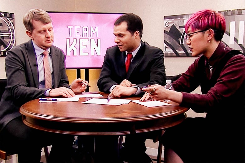 "Ken Jennings, Matt Jackson, and Monica Thieu conferring at a round table. A TV screen in the background reads ""TEAM KEN."""