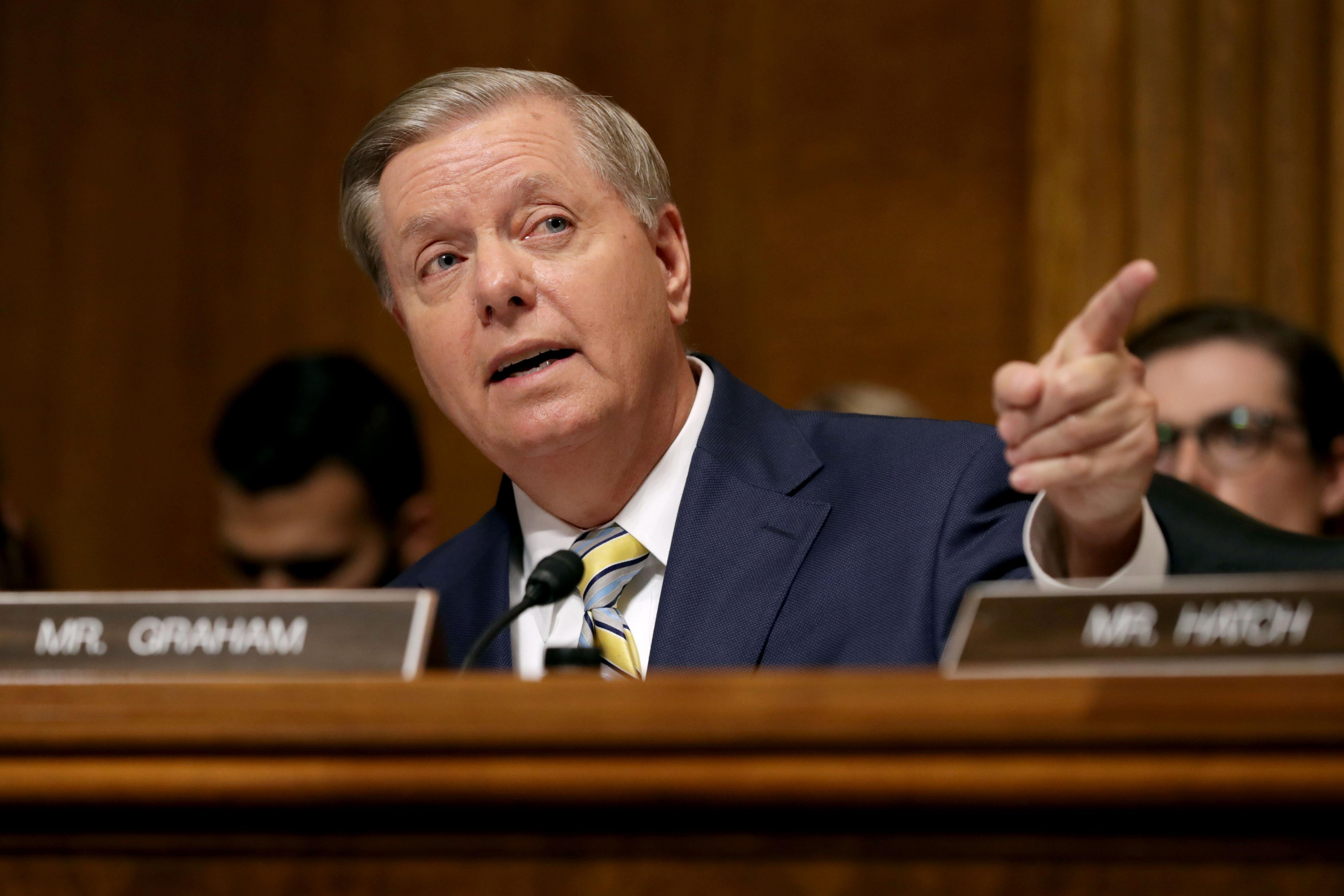 Sen Lindsey Graham points while speaking. A nameplate sits in front of him.