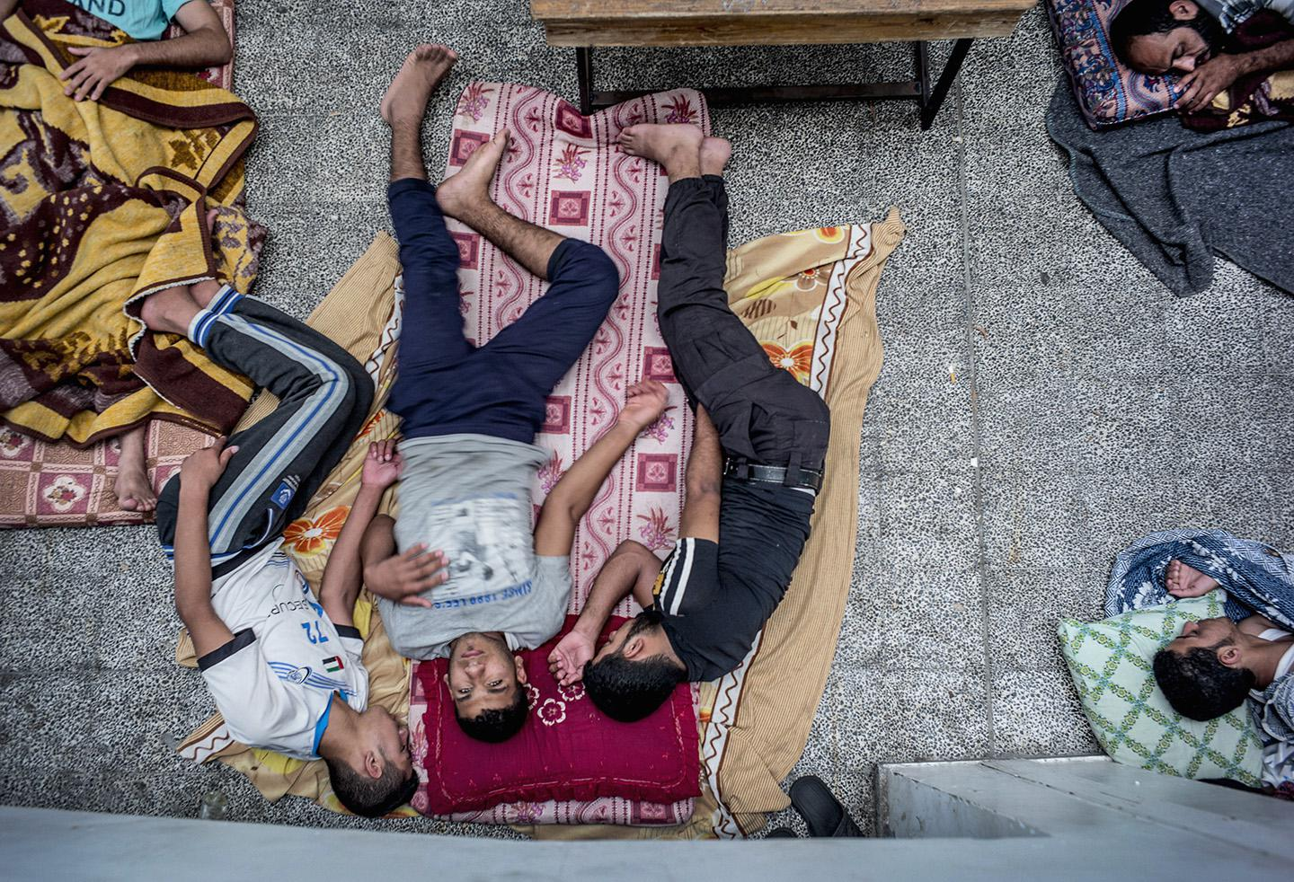 Palestinian men rest as dozens of displaced families.