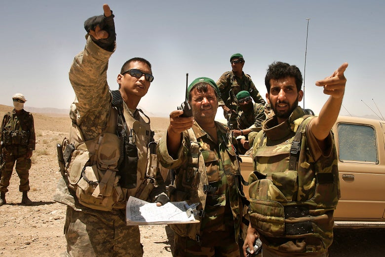 An American troops and two Afghan soldiers point ahead into the distance.