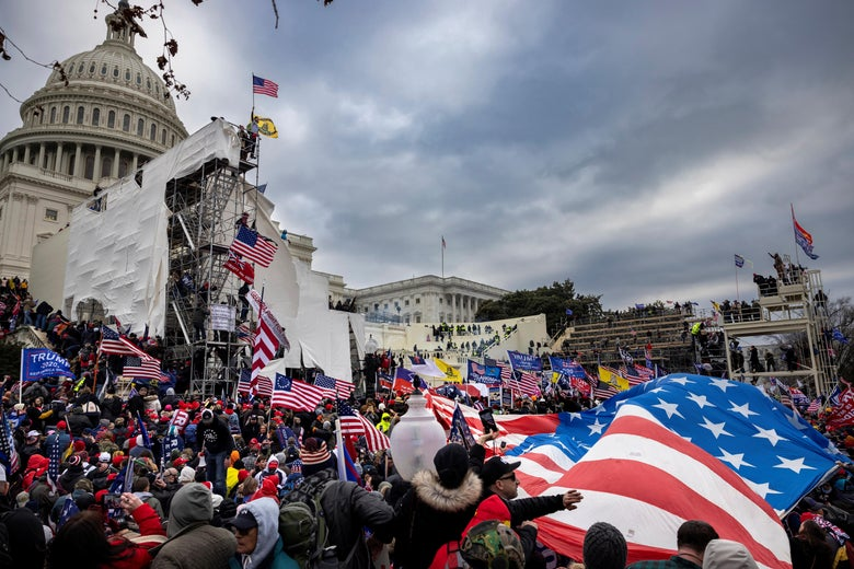 A huge American flag billows in the lower right foreground, overlooked by the Capitol dome in the upper left background, as a crowd bearing various U.S. and Trump flags swarms around the inauguration scaffolding outside the Capitol.