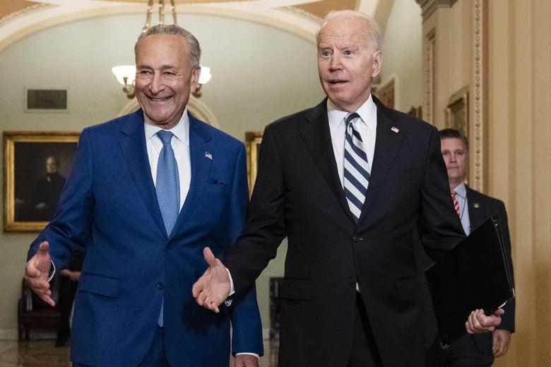 Chuck Schumer and Joe Biden walk down an ornate hall in the Capitol.