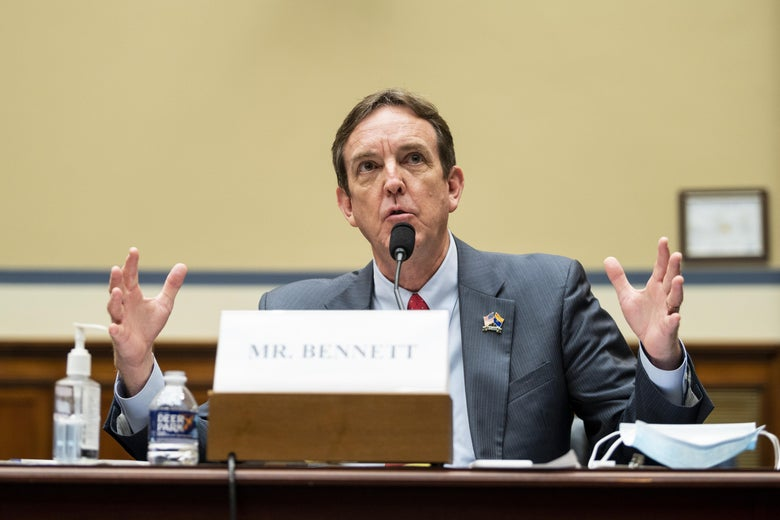 Ken Bennett gestures with both hands as he speaks at a mic while seated on a panel