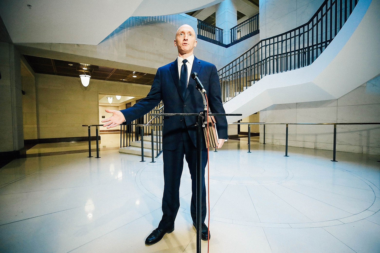 Carter Page standing at a microphone in a big open room.