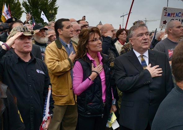 Former Vice Presidential candidate Sarah Palin, center, and Sen. Ted Cruz (R-TX), center left, hold their hands over their hearts during the national anthem as veterans, their families and supporters hold a rally at the WWII Memorial to protest its' closing on October, 13, 2013 in Washington, DC.