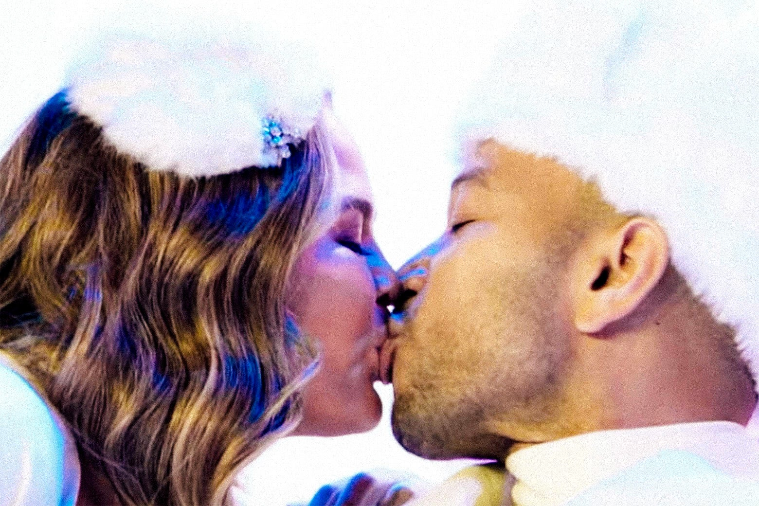 Chrissy Teigen and John Legend kiss while wearing Santa outfits.