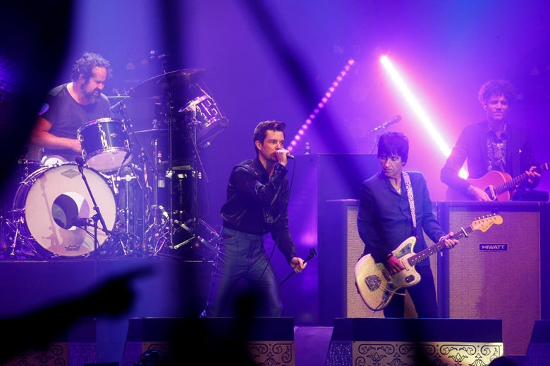 Johnny Marr performing with The Killers.