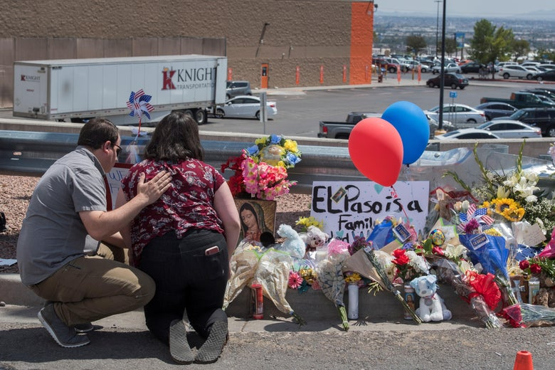 "Two people kneel beside a memorial of flowers, balloons, and religious items honoring the victims of the shooting. A sign says ""El Paso is a family."""
