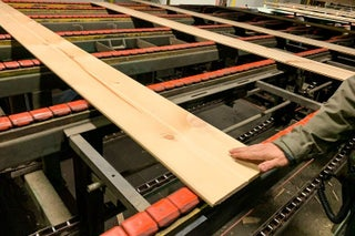A finished board comes off the line at Robbins Lumber.