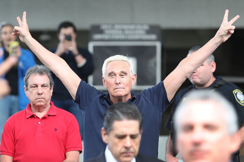 Roger Stone, wearing a navy-blue polo shirt, holds both arms in the air, making the two-finger peace sign with each hand.