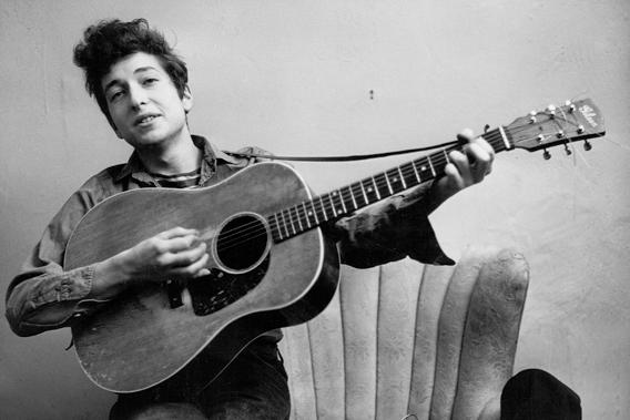 Bob Dylan poses for a portrait with his Gibson acoustic guitar in September 1961 in New York City
