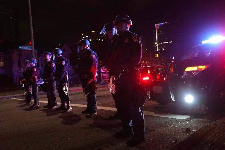 Police officers wearing face shields and holding zip ties stand in a row at night