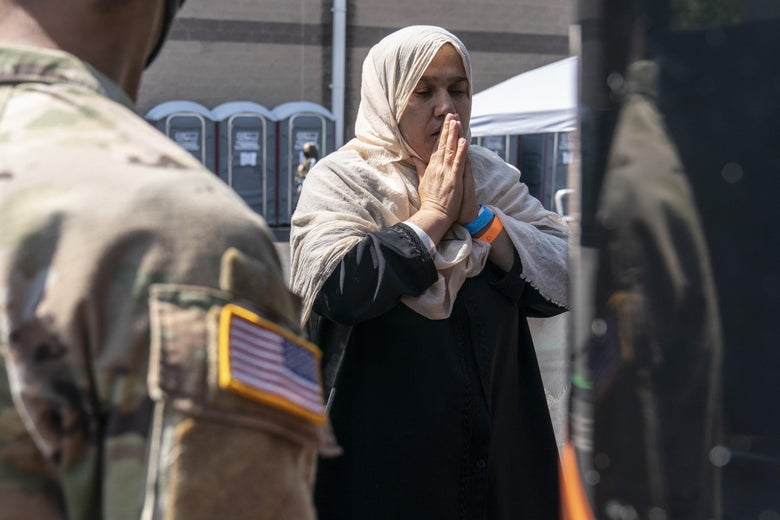 A woman stands with her hands clasped in prayer next to a bus. A U.S. service member in fatigues stands in the foreground, facing her.
