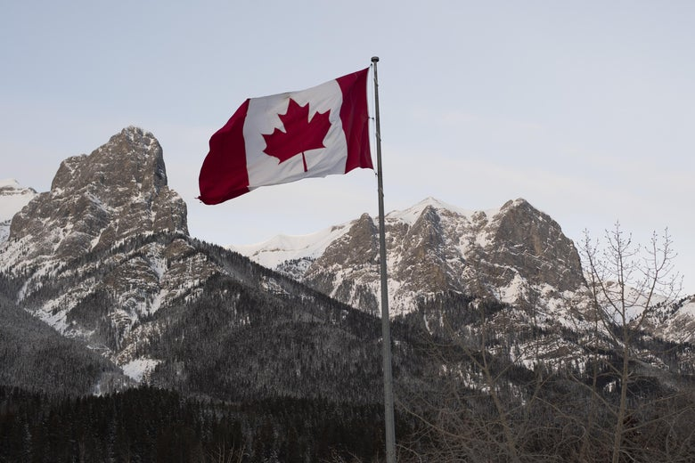 The Canadian flag flies over the Canadian Rockies.
