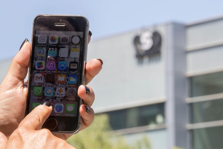 a pair of hands holds an iPhone up in front of an office building.