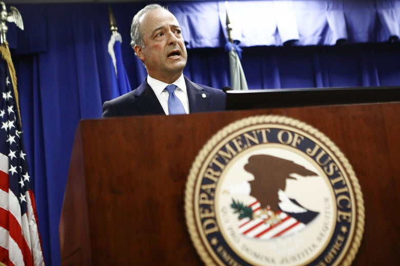 Hanna, wearing a suit, speaks at a lectern decorated with the Department of Justice seal.