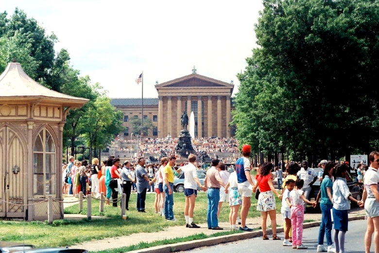 People hold hands in a line through a park in Philadelphia.