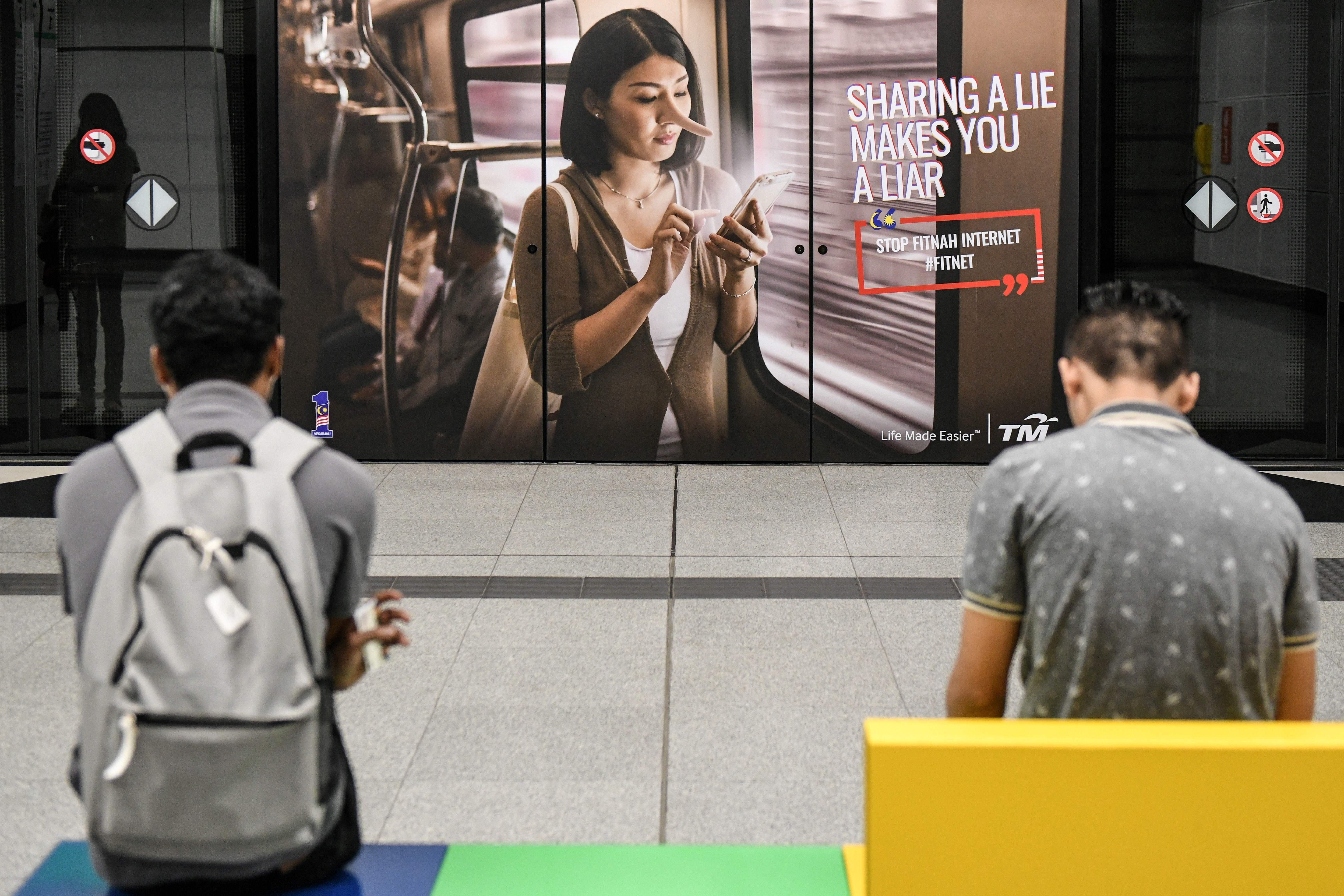 "Commuters wait for the train in-front of an advertisement reading ""Sharing a lie makes you a liar"" at a train station in downtown Kuala Lumpur on March 26, 2018."