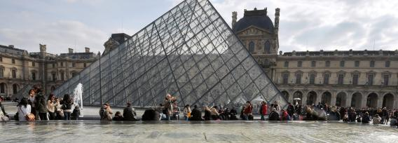 People enjoy the sunny spring weather near the Louvre Pyramid at the Cour Carree of the Louvre Museum on April 7, 2013, in Paris.
