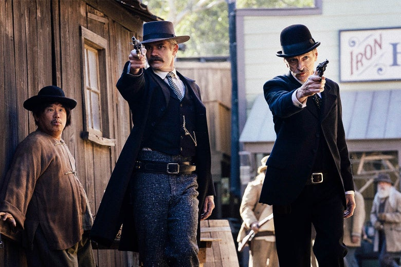 In a scene from Deadwood: The Movie, Timothy Olyphant and John Hawkes as Seth Bullock and Sol Star, aiming guns as they walk through town.