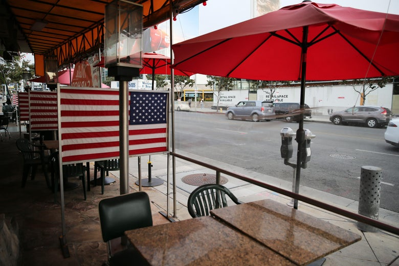Empty outdoor dining tables with umbrellas and American flag dividers between them