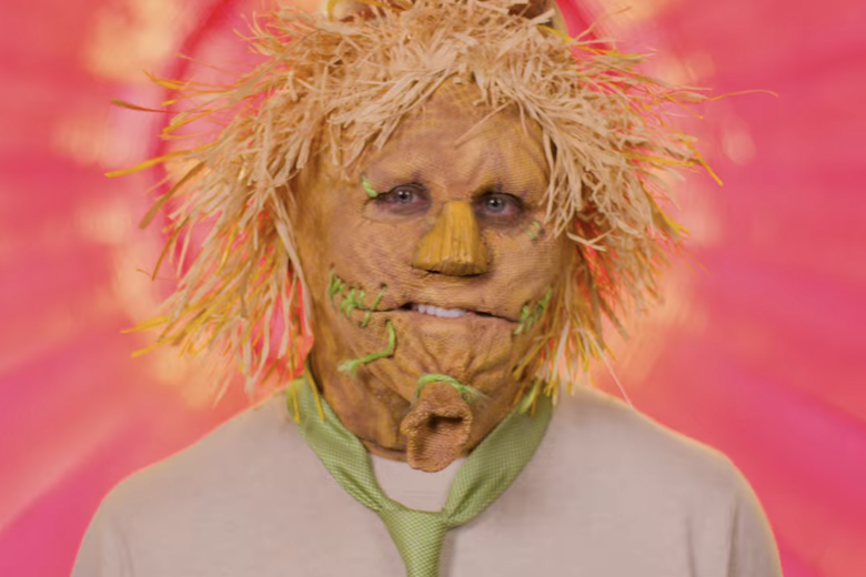 Man in white shirt wearing a scarecrow mask.