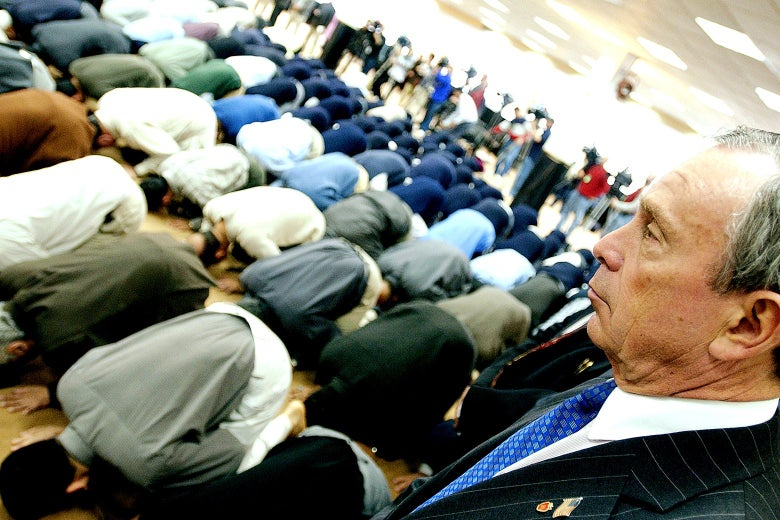 Michael Bloomberg looks over Muslims kneeling in prayer.
