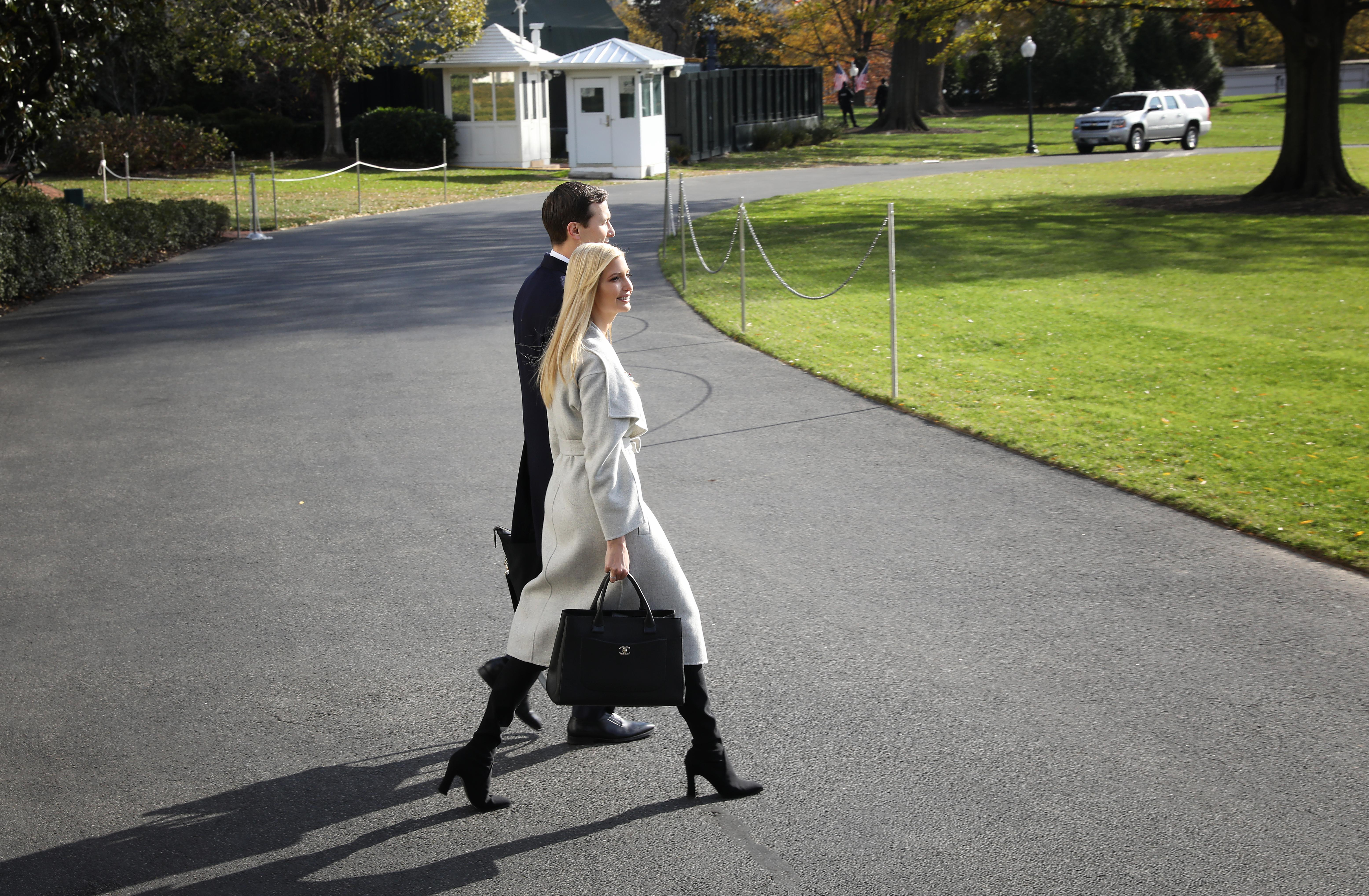 Ivanka Trump and Jared Kushner walk across the White House lawn.