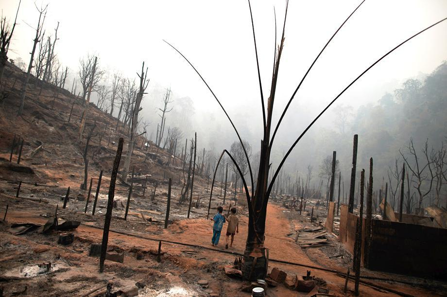 Two boys walk through the ruins of the Ban Mae Surin refugee camp near Mae Hong Son, Thailand, on March 24, 2013. At least 42 people have died in a fire at a camp that is home to thousands of refugees from Burma.