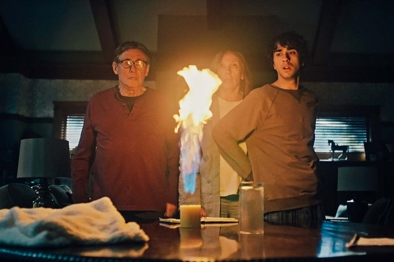 Gabriel Byrne, Toni Collette, and Alex Wolff stand around a table with an object on fire on top in Hereditary.