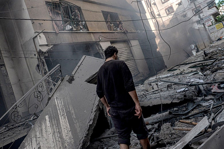 A man walks amongst the aftermath of targeting Al-Jawhara Tower in central Gaza on Wednesday in Gaza City.