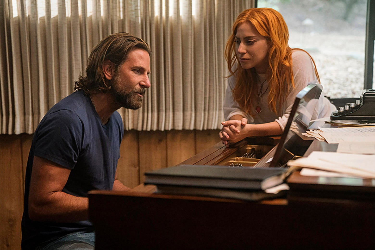 Bradley Cooper plays at the piano as Lady Gaga leans over.