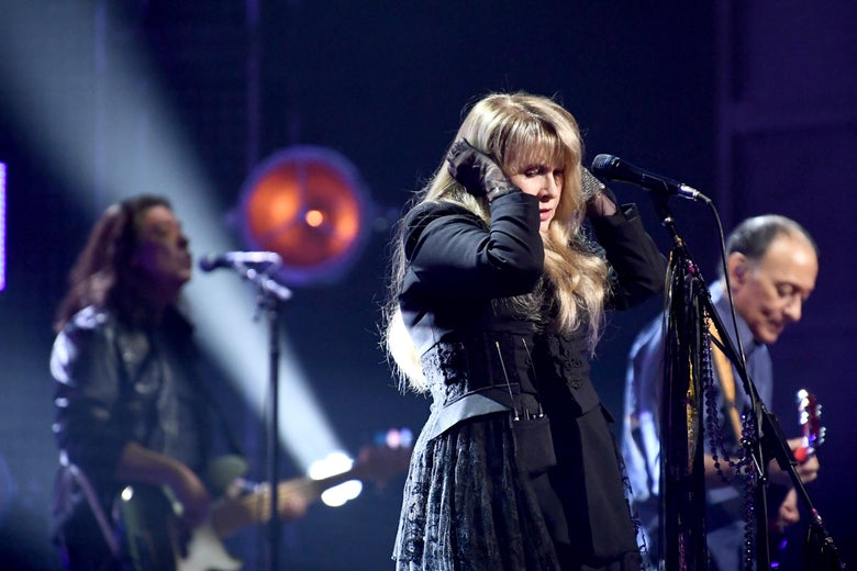 A singer puts her hand on her head while singing. Two male guitarists are shown blurry in the background of the image.