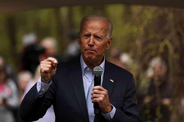 Biden, wearing a suit coat without a tie, speaks outdoors.