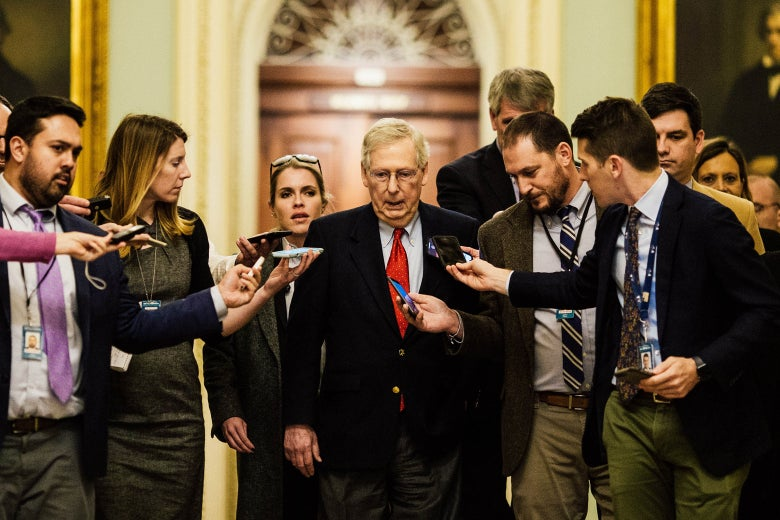 McConnell surrounded by reporters holding their phones out, trying to get a quote from him.
