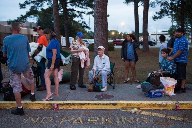 People line up on the sidewalk alongside a no parking zone.