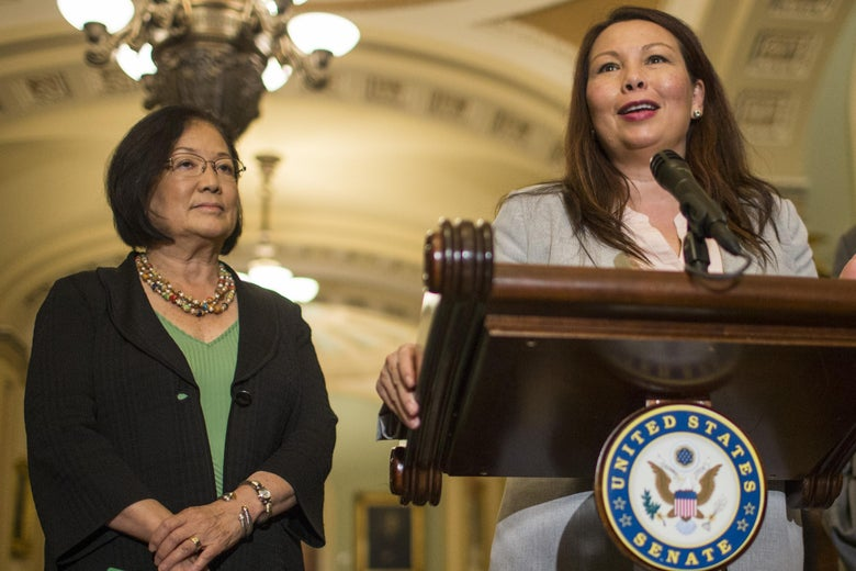 Mazie Hirono stands beside Tammy Duckworth who is speaking at a podium inside the Capitol
