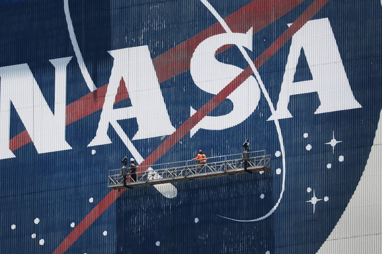 Two people on a scaffolding in front of a giant NASA logo