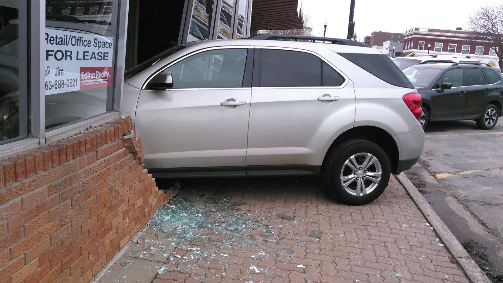 A car surrounded by shattered glass that has crashed through the front of a building.