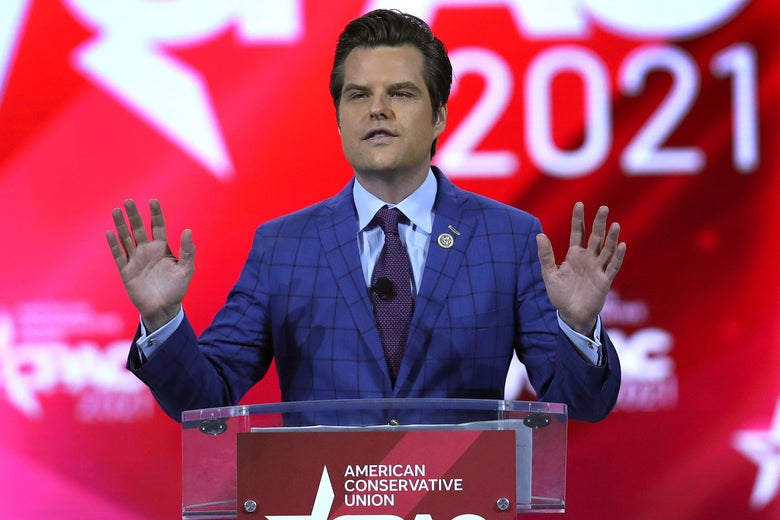 Matt Gaetz holds both hands up as he speaks behind an American Conservative Union podium onstage