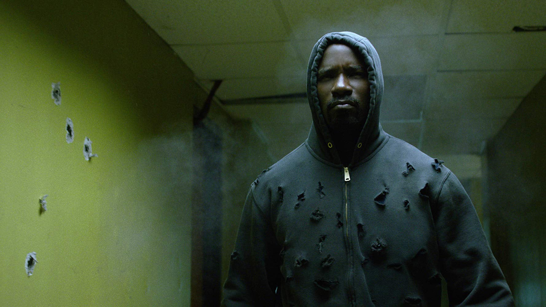 Mike Colter as Luke Cage, striding toward the camera in a hoodie that has been shot to pieces.