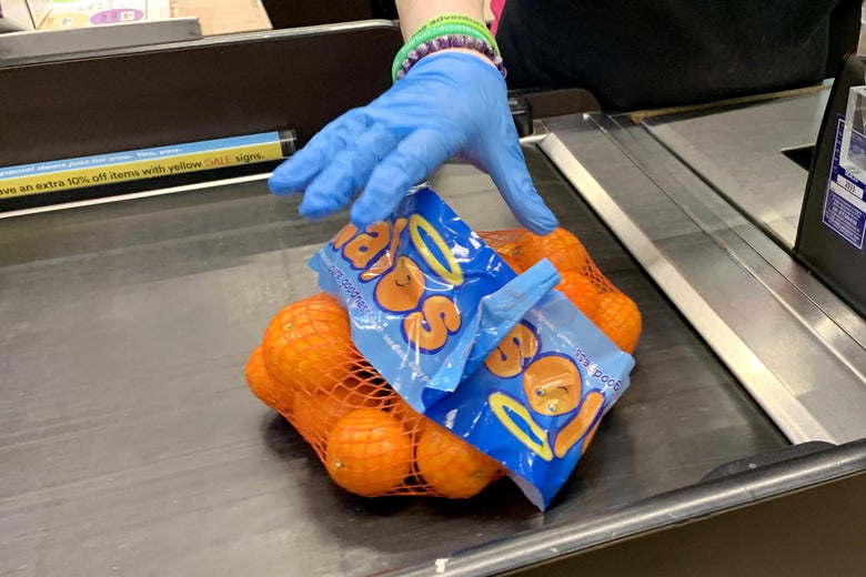 CAMBRIDGE, MASSACHUSETTS  - MARCH 23: A cashier wears gloves at Whole Foods on March 23, 2020 in Cambridge, Massachusetts. Massachusetts Governor Charlie Baker ordered all non-essential businesses to close by noon on March 24 in an attempt to stop the spread of COVID-19.  Grocery stores and pharmacies will remain open, and restaurants will still be able to sell food for take-out service. (Photo by Maddie Meyer/Getty Images)