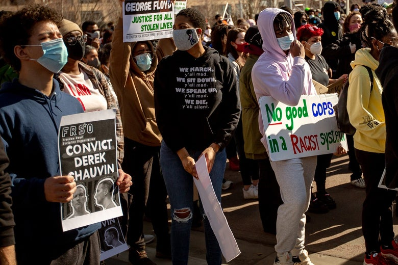"""Crowd of protesters in Minneapolis. One person holds a sign that says """"Convict Derek Chauvin."""""""