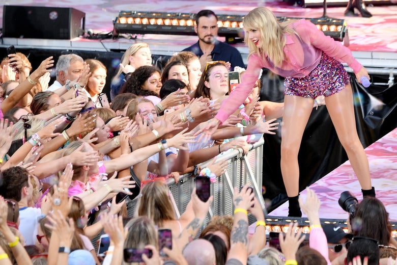 Taylor Swift leans down from a stage to touch fans' hands.