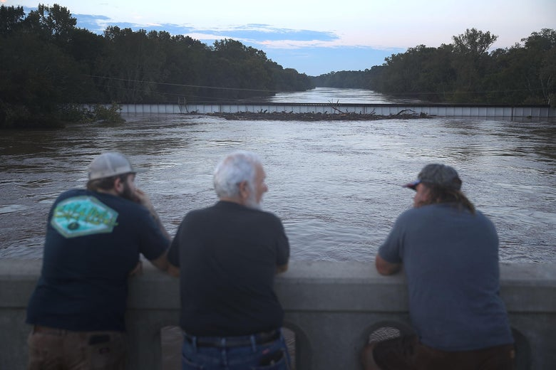 People look on at the the Cape Fear river as it crest from the rains caused by Hurricane Florence as it passed through the area on September 18, 2018 in Fayetteville, North Carolina. The area was inundated with rain that caused concern for large scale flooding in the North Carolina and South Carolina area.  (Photo by Joe Raedle/Getty Images)