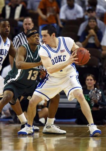 J.J. Redick #4 of the Duke Blue Devils handles the ball under pressure from Maurice Ager #13 of the Michigan State Spartans.