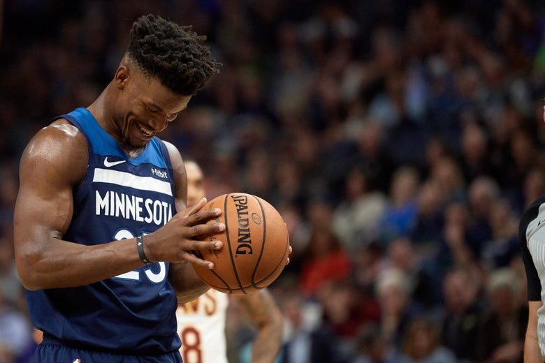 Jimmy Butler holds a basketball, preparing to shoot a free throw.
